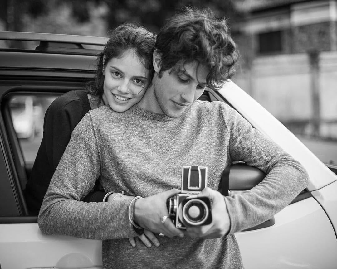 Laura Neiva abraça Chay Suede, que segura uma câmera fotgráfica antiga. Em preto e branco.