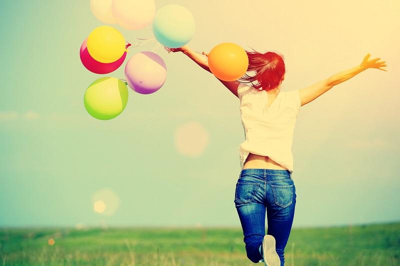 Garota de costas correndo na grama com balões voando perto