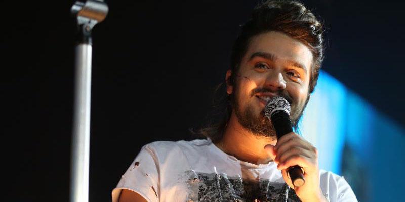 uma imagem com a foto do cantor Luan Santana cantando