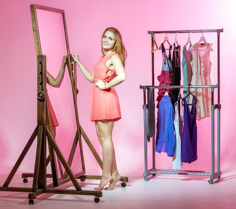 Menina de frente para o espelho num fundo rosa