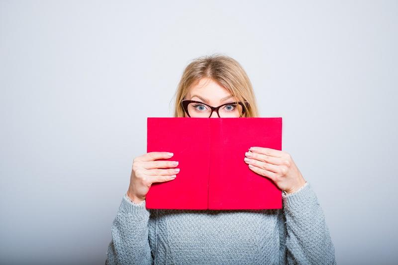 menina loira de óculos segurando um livro de capa vermelha