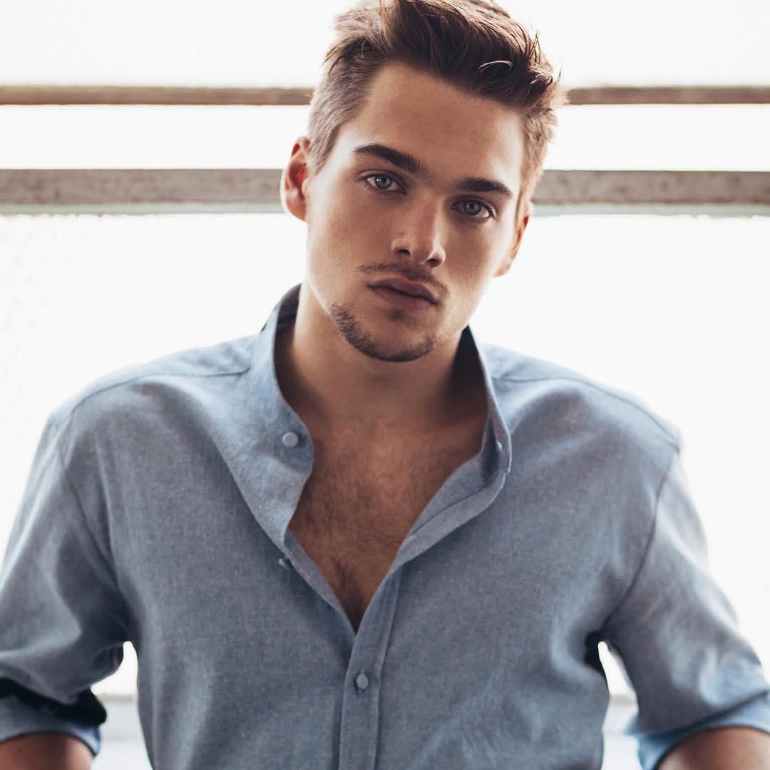 ator de Teen Wolg Dylan Sprayberry vestindo camisa azul clara