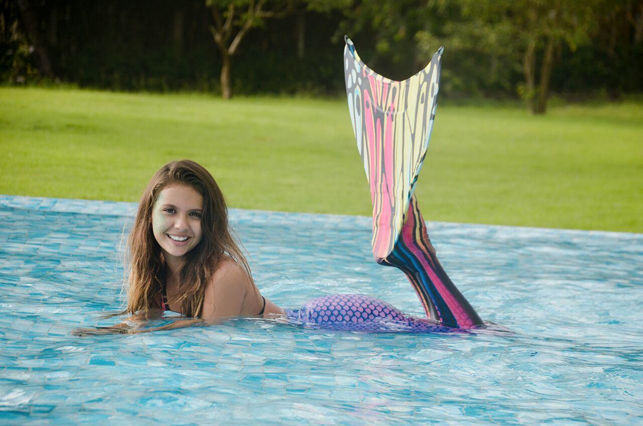 menina usando cauda de sereia posa em piscina