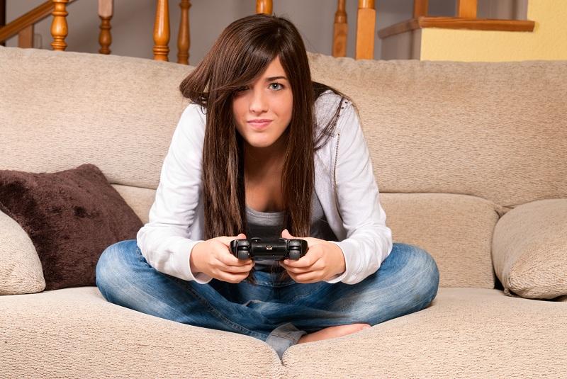 Menina jogando vídeo game de pernas cruzadas no sofá pensando nos canais mais nerds