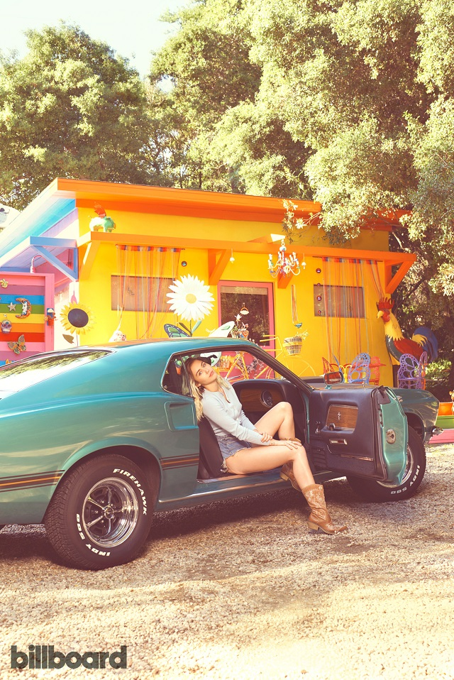 Miley aparece sentada em carro verde, em cenário arborizado