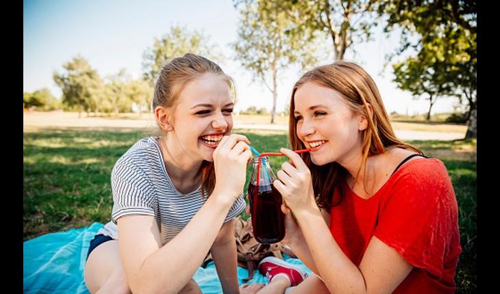 Amigas sorrindo enquanto tomam suco