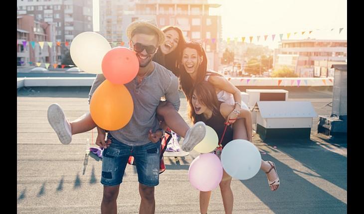duas meninas e um rapaz segurando balões e sorrindo