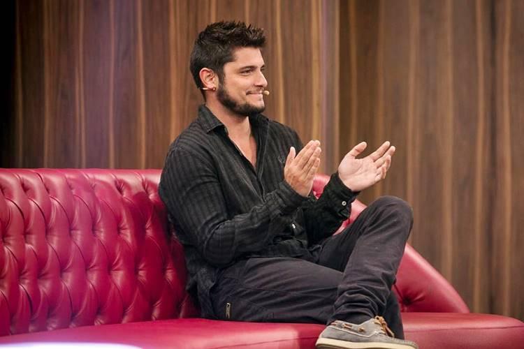 Bruno Gissoni bate palmas sentado no sofá vermelho do estúdio onde é gravado o programa Tamanho Família
