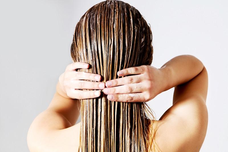 Menina de costas com o cabelo loiro e liso cheio de creme