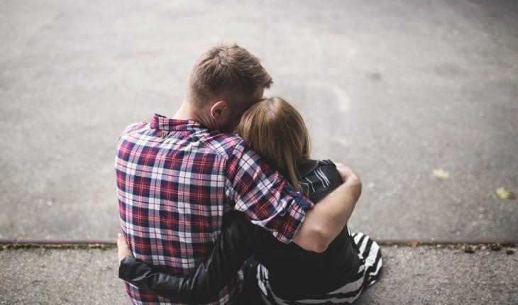 casal abraçado sentado no chão