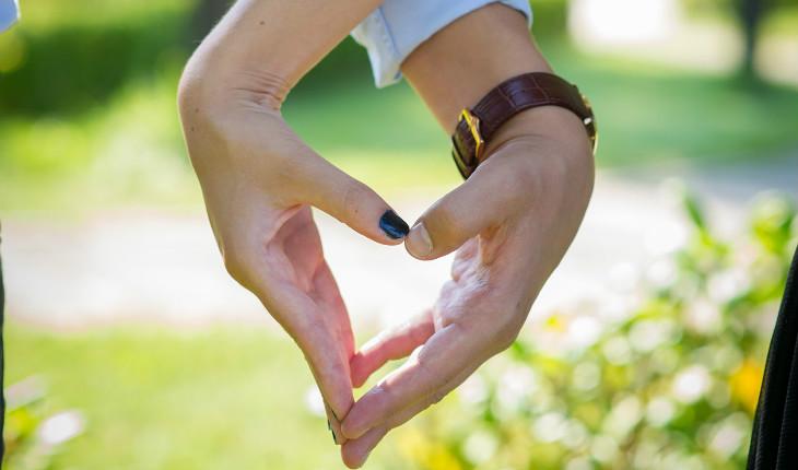 casal de mãos dadas fazendo um coração