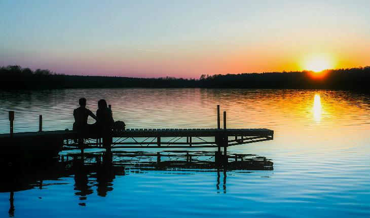 casal sentado olhando para a água