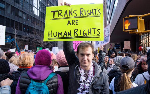 """Transgêneros: pessoa levanta em manifestação um cartaz que diz """"Direitos Trans são direitos Humanos"""""""