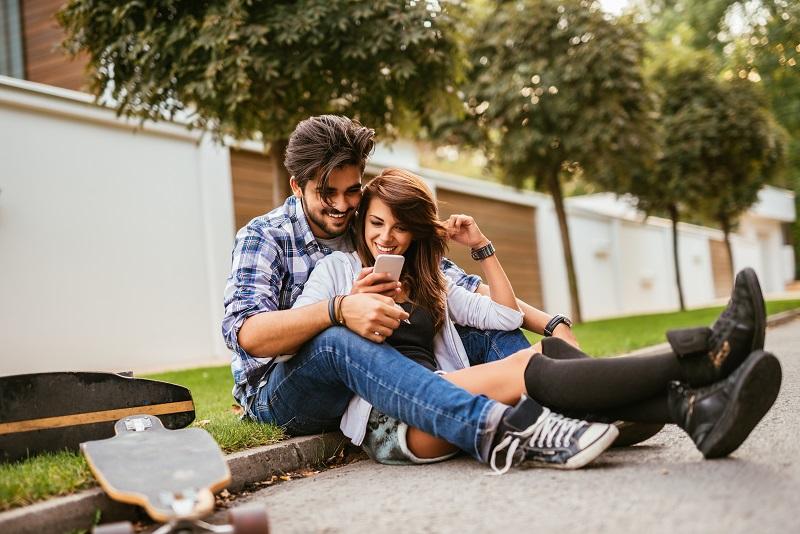 Casal de menina e menino sentados na sarjeta olhando o celular e rindo
