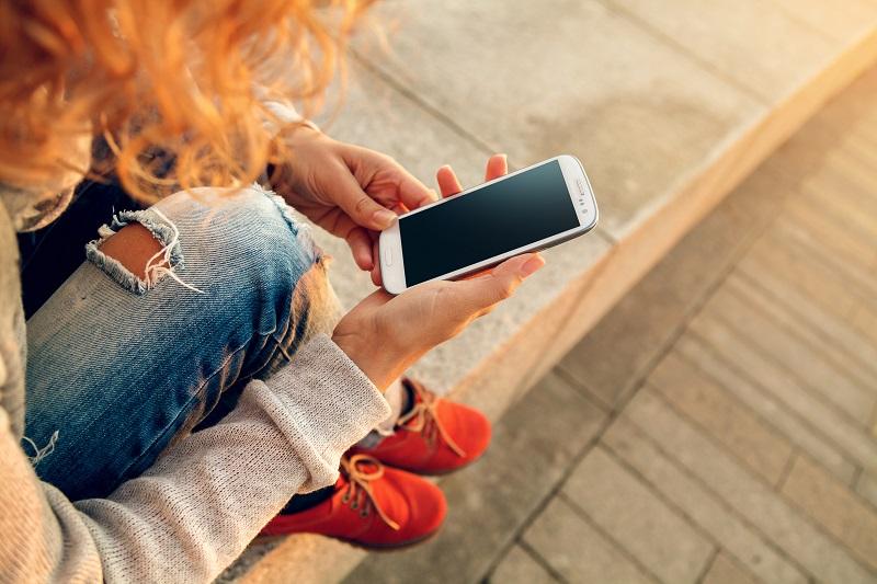 Menina ruiva com celular na mão