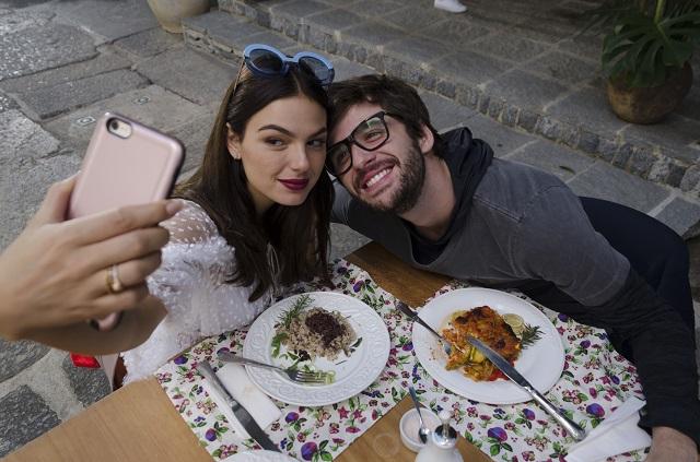 Isis Valverde e Gil Coelho tirando selfie na mesa com comida