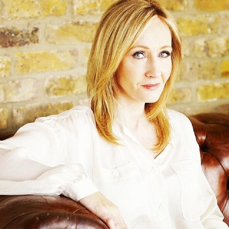 J. K. Rowling olha para a câmera, sentada, usando camisa branca