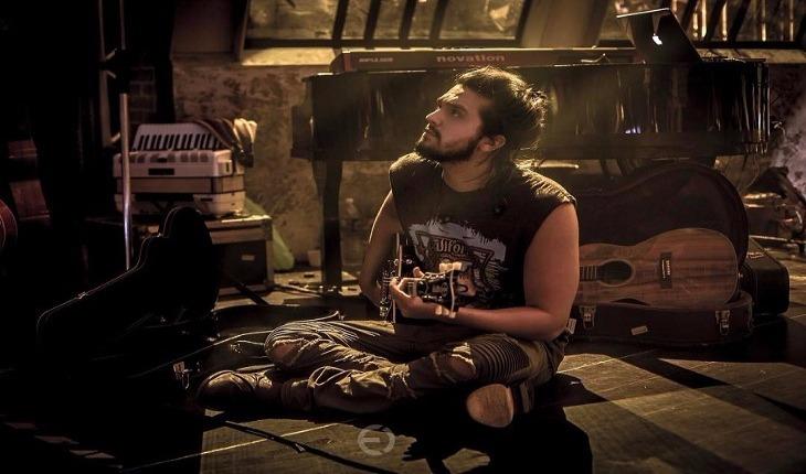 Luan Santana setado no chão tocando violão