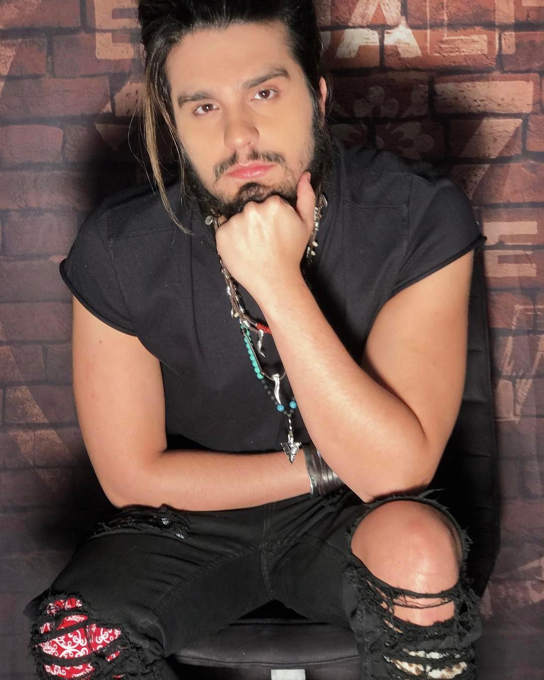 Luan Santana usa camiseta preta, olhando para a câmera e com a mão apoiando o rosto