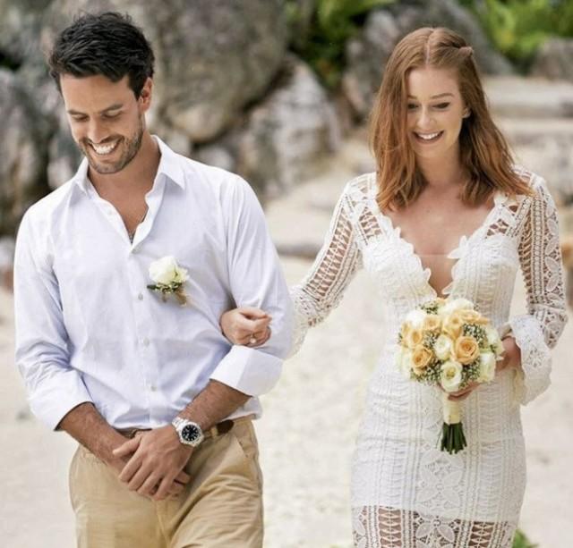 marina ruy barbosa anda de mãos dadas com noivo, usando vestido rendado branco