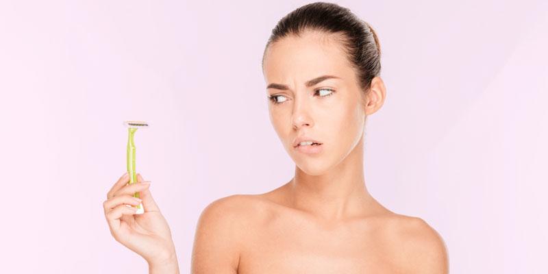 menina olha para uma lâmina de depilação