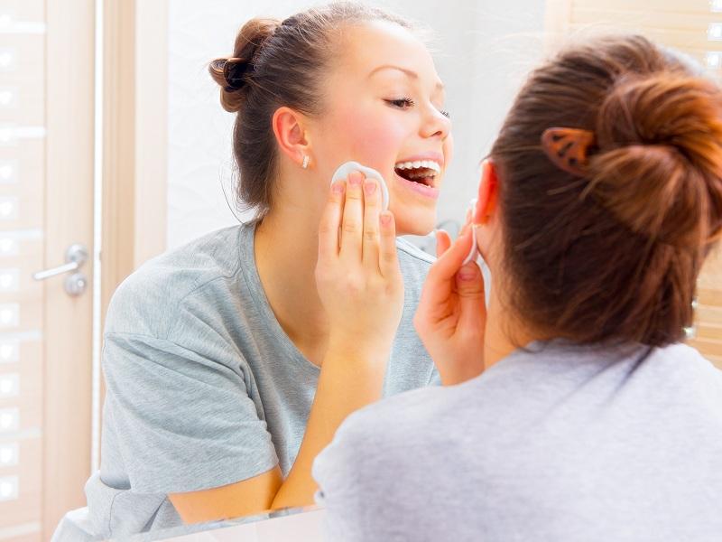 Menina limpando a pele de frente para o espelho sorrindo