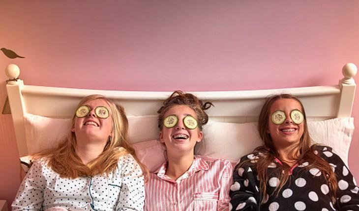 três amigas deitadas com pepinos nos olhos