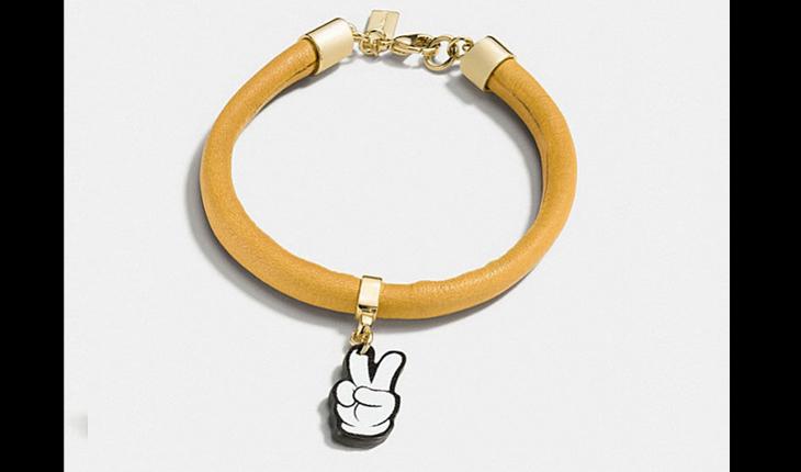 pulseira amarela com pingente da mão do mickey mouse fazendo sinal de paz e amor