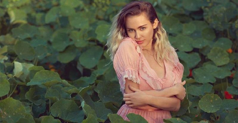 Miley aparece com os cabelos compridos e soltos, usando um vestido rosa claro, em meio a um jardim