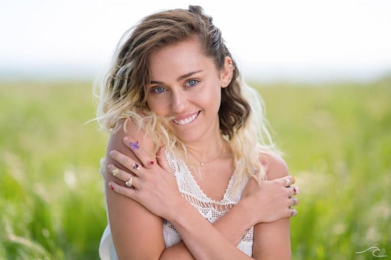Miley Cyrus sorri usando vestido branco em meio a campo e dia claro, Malibu