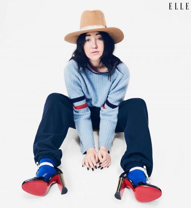 Noah Cyrus sentada no chão usando salto vermelho, meias azuis, moletom e chapéu