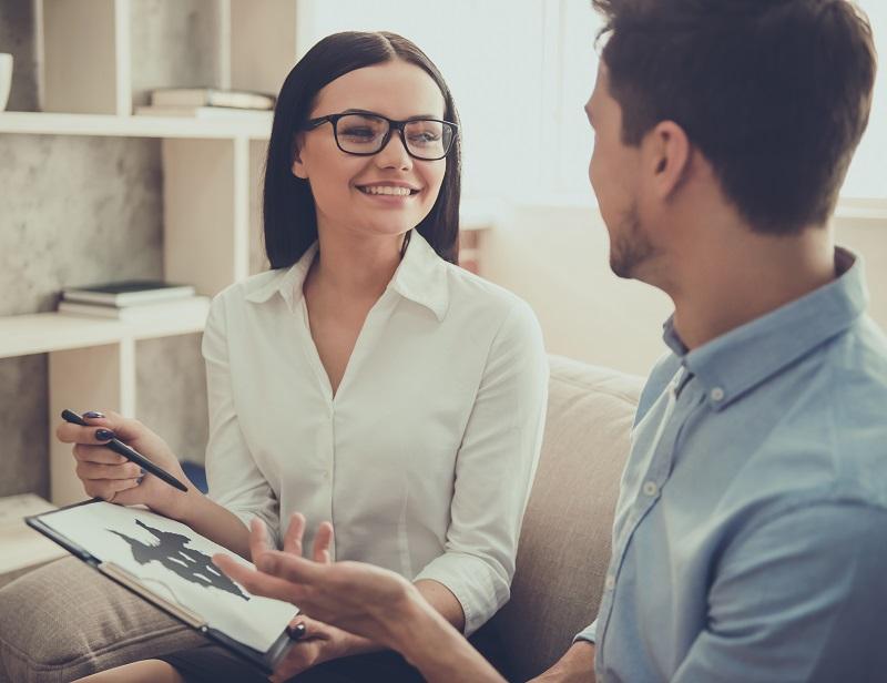 Homem se consultando com uma psicóloga sorridente