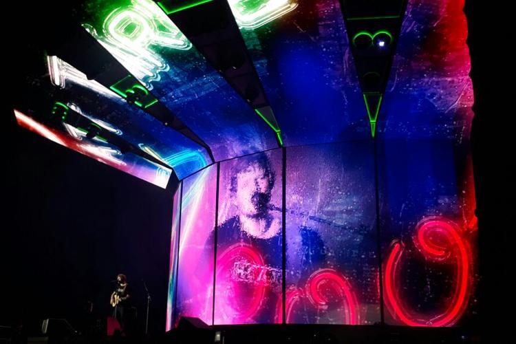 Show do Ed Sheeran. O cantor está no palco, enquanto sua imagem está no telão atrás.