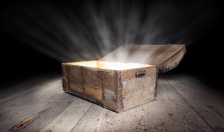 Baú de tesouro aberto com uma luz saindo