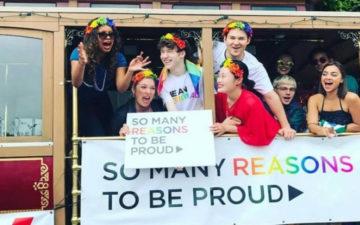 """elenco de 13 reasons why segurando plaquinha que diz """"muitas razões para se orgulhar"""", usando acessórios com as cores do arco íris"""