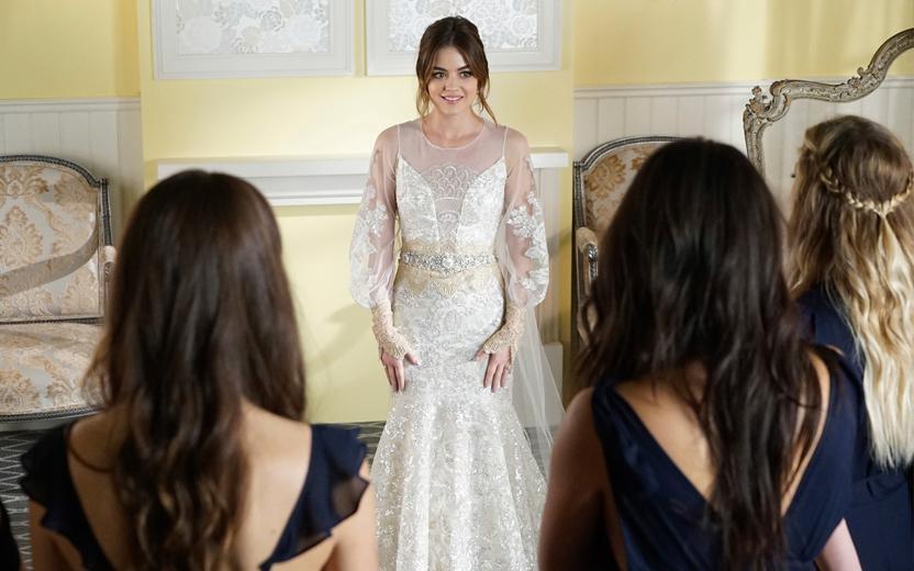 Aria usando vestido de noiva branco rendado com mangas transparendes e levemente bufantes. Outras Liars aparecem na foto de costas, olhando para Aria