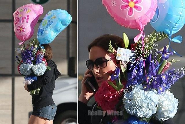 Mulher segurando um balão rosa e um azul