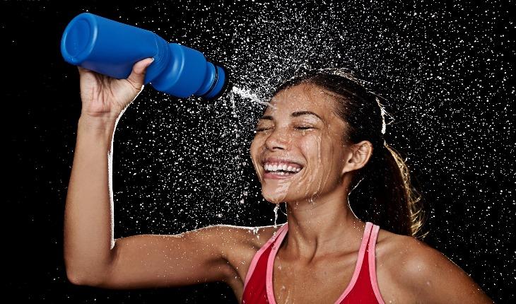 Menina com squeeze jogando água no rosto