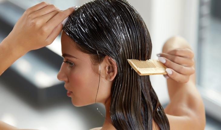 Menina passando pente no cabelo cheio de creme