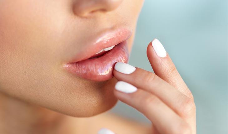 Passando hidratante nos lábios, rosto cortado
