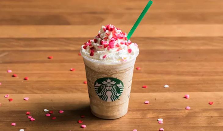 frappuccino marrom claro com chantilly e confeitos em formato de corações rosas em cima