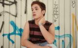 João Guilherme sentado em frente a uma parede com pichações. Ele usa uma camiseta regata listrada em marrom e preto e olha para o lado, com a mão no pescoço