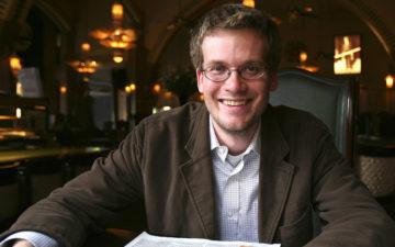 John Green sorri sentado em mesa de lugar que parece ser uma biblioteca. Ele usa camisa branca e casaco marrom