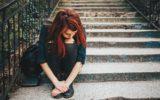 Menina triste e cabisbaixa na tpm