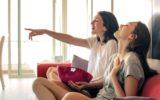 meninas assistindo tv sentadas em sofá, comendo pipoca e rindo