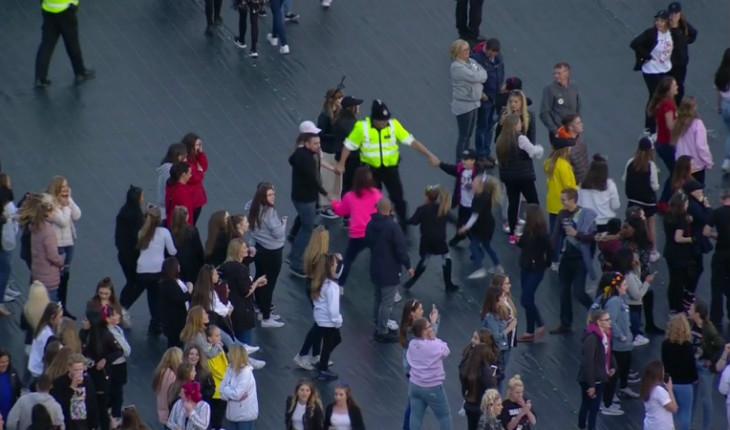 policial brincando com crianças durante o show da Ariana Grande