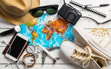 mapa, tênis, celular, óculos de sol, câmera fotográfica e outros objetos de viagem sobre fundo branco