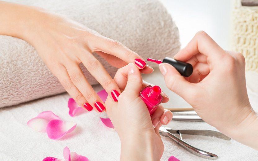 Moça pintando as unhas com a cor de esmalte rosa