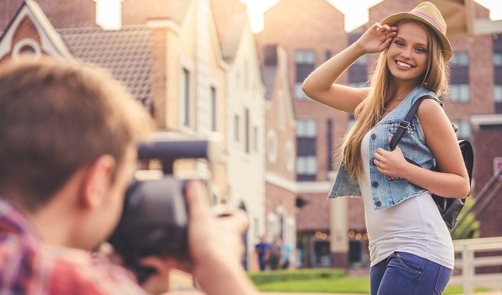 Menina fazendo pose para ser fotografada pelo moço