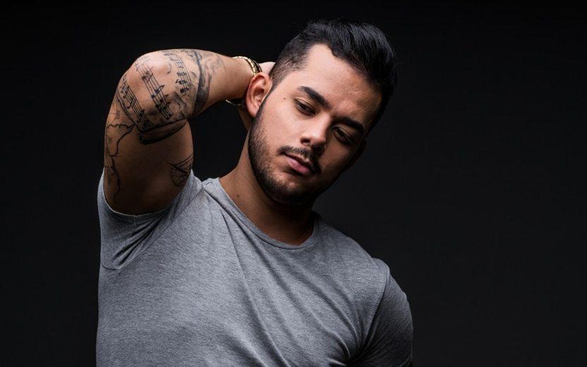 Higor Rocha usa camiseta cinza e exibe tatuagens no braço em fundo preto